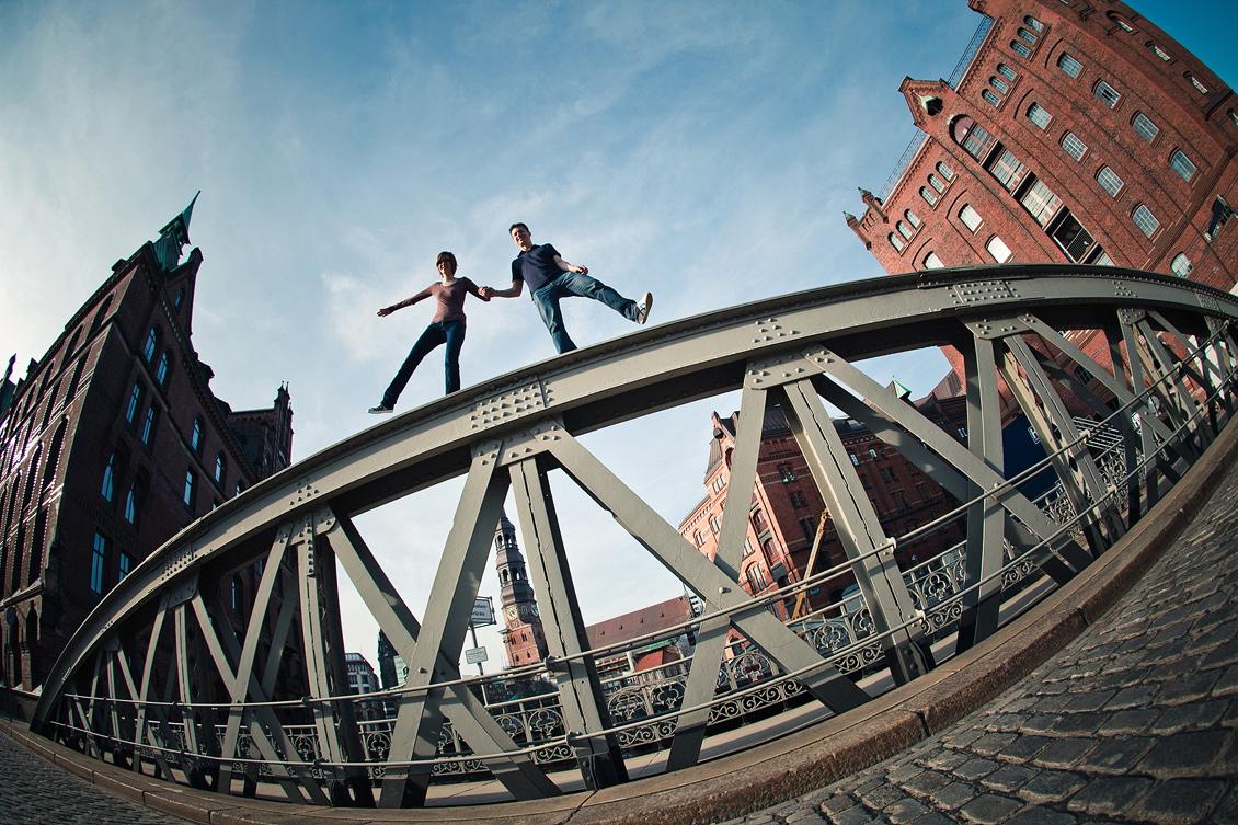 Engagement_shooting_hafencity_Hamburg_das_Paar_balanciert_auf_der_Pickhuben_Brücke